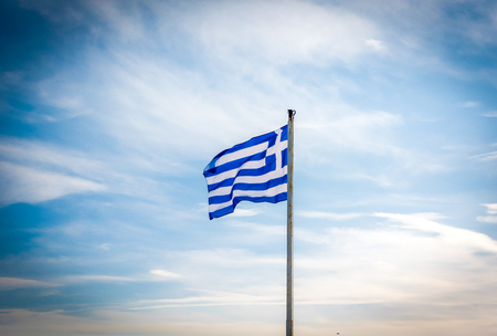 dramatic clouds: Greek flag waving in the wind in a blue sky and white clouds around Stock Photo