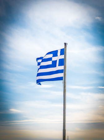 wind dramatic sky: Greek flag waving in the wind in a blue sky and white clouds around Stock Photo