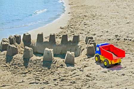 cartoon wood bucket: Childens truck plastic toy with sand castle on the beach Stock Photo
