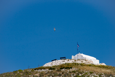 Typical greek white small cahapel on the top of a hill. A seaguul flying above. Low angle view