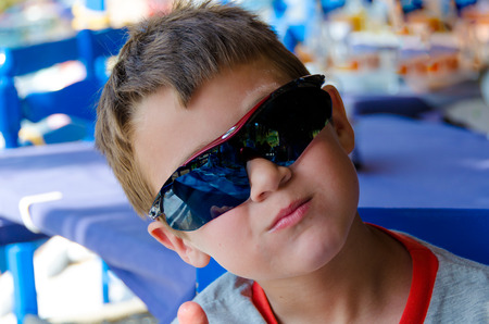 Little boy with sunglasses and t-shirt at a taverna in Greece during vacations Stock Photo