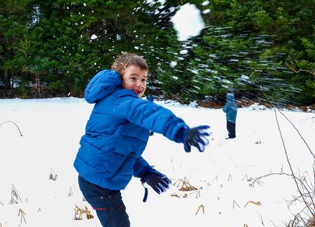 palle di neve: Il ragazzo in blu caldo cappotto divertirsi in posto bellissimo inverno con le palle di neve