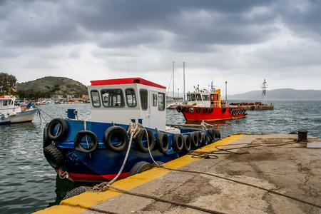 A rainy wintry day under a heavy sky. Fishing boats at the small harbor. Pachi,Greece