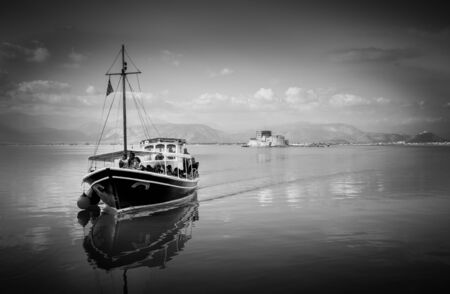 bourtzi: Nafplio,Bourtzi, Greece - December 27, 2015: Boats with tourists,sailing in calm waters of the Argolic Gulf, Greece. Sunrays reflect through blue green sea water.In the background the historic small island named Bourtzi, an old castle with prisons
