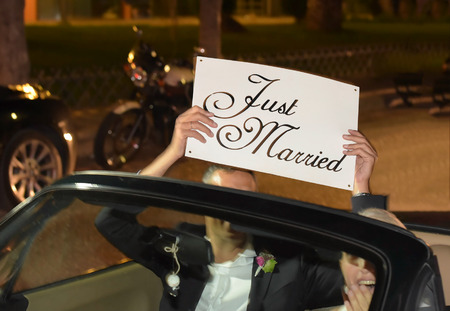 A newlywed couple is driving a convertible modern car on a road for their honeymoon. The bride is driving and the husband holding a just married placard, front view