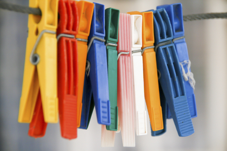 colored clothepins hanging on black rope on a blurred background , closeup capture