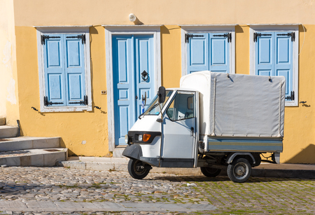 SYROS island- GREECE.APRIL 4 -2015:A Piaggio mini white truck with three wheels ,ideal for delivering and small business in small streets such as shown in the photo .Syros island,Cyclades,Greece Editorial