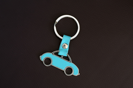 Key chain with cyan beetle car on dark leather pad as background