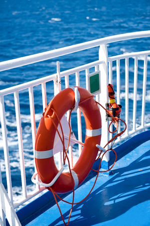 Ring life boy on ferry while traveling to an island. Obligatory ship equipment.Orange lifesaver on the deck of a cruise ship.