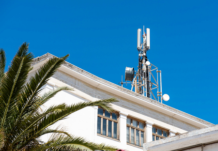 Cell phone telecommunications antennas and repeaters on building against clear blue sky 版權商用圖片