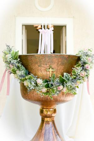 Orthodox Baptism Bowl prepared for christening ceremony in greek church. White vignette