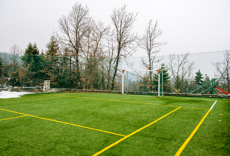 Field for soccer and other sports with trees and snow at Winter