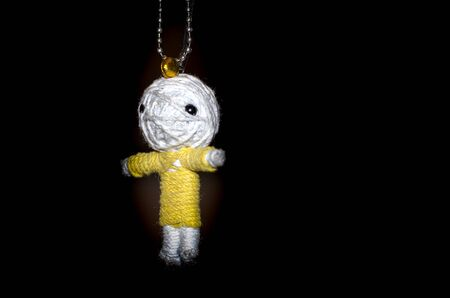 Cute little doll isolated on black background. Charm keychain for a children bag. Kids sewing crafts idea Stock Photo