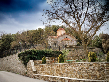 Small church on the hill with trees and stone made hedges around. Arcadia. Greece