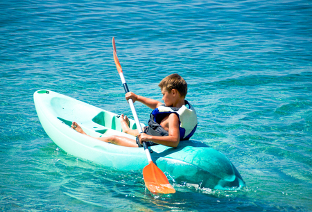 Active  boy, having fun enjoying adventurous experience kayaking on the sea , a sunny day during summer vacation in greek island