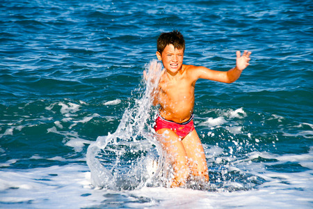 Little sunburnt boy enjoy his Summer vacation in the sea, swimming and play with the waves