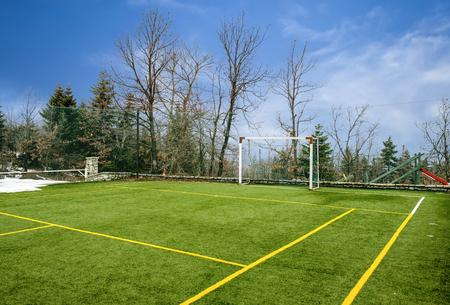 Veld voor voetbal en andere sporten onder de blauwe hemel met wolken in de winter