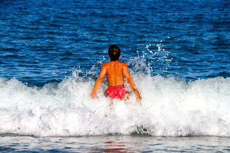Little sunburnt boy enjoy his Summer vacation in the sea, swimming and play with the waves splashing over him. Stock Photo