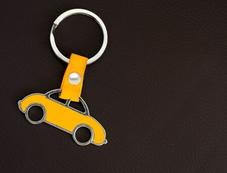 Key chain with yellow car on dark leather pad as background. Stock Photo
