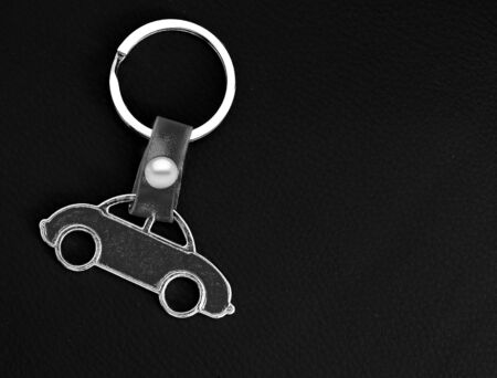 Key chain with car on black leather pad as background.