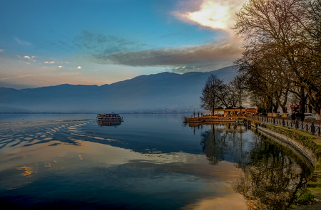 Sunset over Ioannina city and lake Pamvotis. seafront street for cars,pedestrians and bicycles .Epirus, Greece.