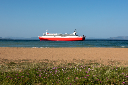 Red ferryboat and beach in Rafina, Greece