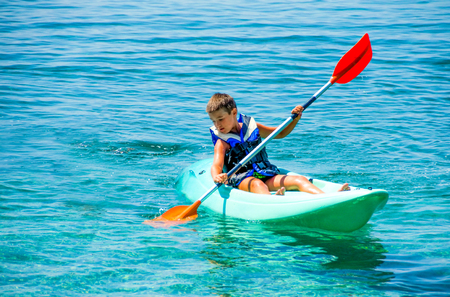 kayaking lessons. Boy with  life buoy suit in kayak lessons during summer vacations in an island of Greece. Stock Photo