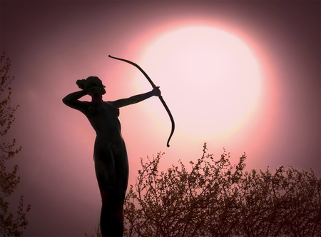 Statue of a woman Archer Silhouette with a bow target the sun