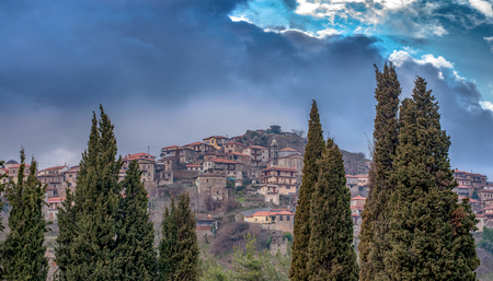 Panoramic view of a beautiful mountain village named Dimitsana under a dramatic sky and fog, Peloponesse, Greece.