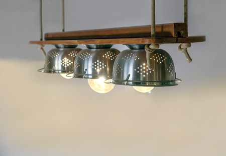 Warm lighting coming out from lamps inside beautiful utensils kitchen equipment, ropes and wood, hanged  from the ceiling Wall clock with forks and spoons on the background. 免版税图像