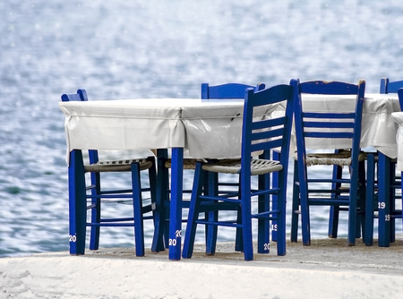 Tables and blue chairs by the seaside. Greece Stock Photo