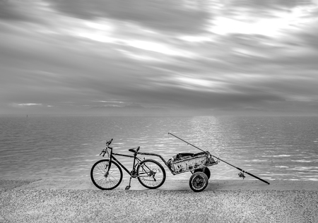 Fisherman's bicycle with trailer on seafront under a dramatic sky. Thessaloniki, Greece Stock Photo