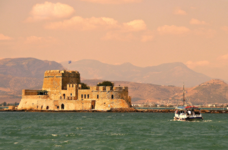 Small wooden boat transfer a group of tourists to Bourtzi island (an ancient prison). Nafplion , Greece.Vintage look e photos