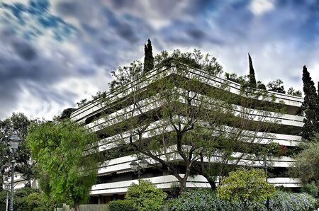 Apartment building n centre of  Athens city with green trees under a dramatic sky in motion Banco de Imagens - 128904867