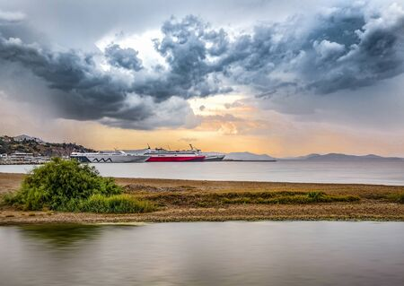 View of Rafina city and port  under a dramatic sky at sunset
