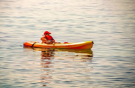 kayaking lessons. Boy with life buoy suit in kayak lessons during summer vacations in an island of Greece.