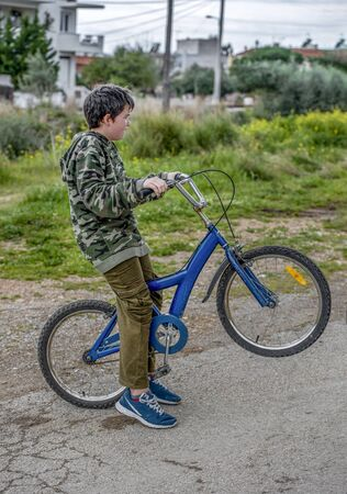 Young child dressed in army clothes  with a bicycle on a walk in the park