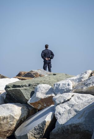 Security man standing alone on big rocks and staring the sea Stockfoto