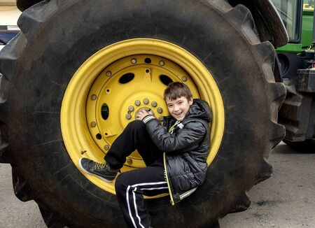 Smiling boy laying in a tractor wheel double his size Stock Photo