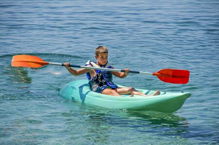 kayaking lessons. Boy with  life buoy suit in kayak lessons during summer vacations in an island of Greece. Stockfoto