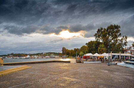 View of tthe harbor and beach in Megalo Pefko (Nea Peramos) under a dramatic sky at sunset,Attica,Greece