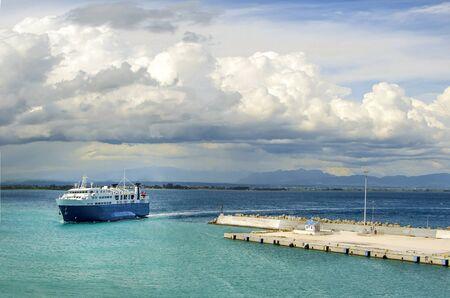 Ferry retournant au port de l'île de Zakynthos, sous un ciel dramatique.Grèce