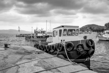 A rainy wintry day under a heavy sky. Fishing boats at the small harbor. Pachi,Greece