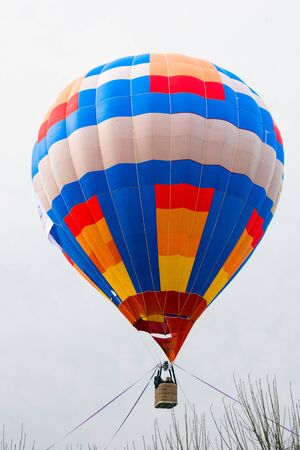 passengers into hot air balloon basket above trees, ready for launch, White background