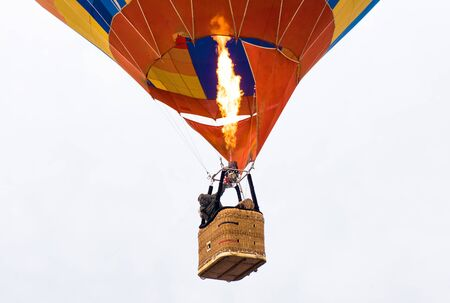 passengers into hot air balloon basket and flames , ready for launch. Isolated in white background Stockfoto