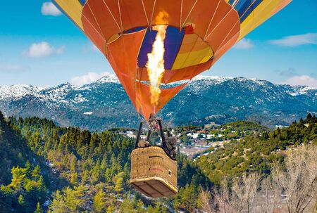 passengers into hot air balloon basket and flames flying from Mainalo to Helmos mountains.Arcadia, Greece Stockfoto