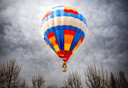 Colorful airballoon in a dangerous flight up above the trees Stockfoto