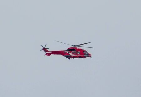 Red rescue helicopter flying on clear sky