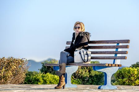 Blonde lady sitting in a bench alone ,staring at the landscape, in a cold winter but sunny day.