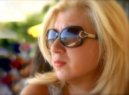 Blonde woman with sunglasses staring the sea.Soft focus
